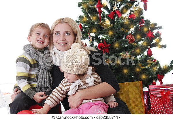 Mother with two children lookig up under Christmas tree - csp23587117