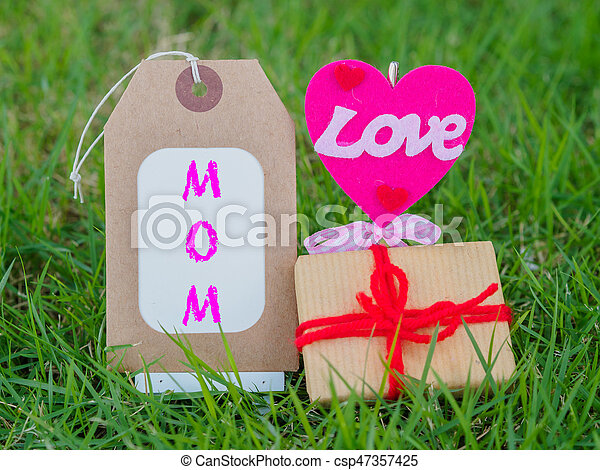 mother's day concept. LOVE MOM text with colorful heart and gift on green grass background - csp47357425