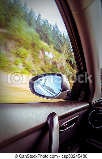 Motion blurred speeding car on country road - csp80245486