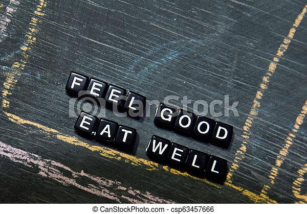 Se siente bien comer bien en bloques de madera. Cruza imagen procesada con fondo de pizarra. Inspiración, educación y conceptos de motivación - csp63457666