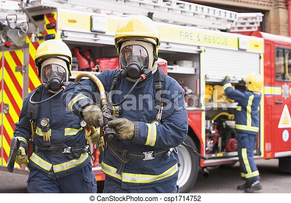Dos bomberos con mangueras y hachas que se alejan de los motores de fuego y de otro bombero de fondo - csp1714752