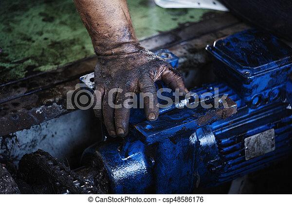 Mano de reparador durante el mantenimiento del motor eléctrico - csp48586176