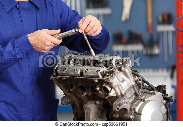 motorcycle mechanic repairing an engine csp53661951