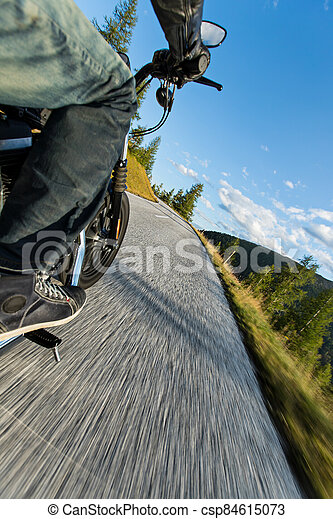 Motorcycle rider driving in Alps, beautiful nature with clear sky. - csp84615073