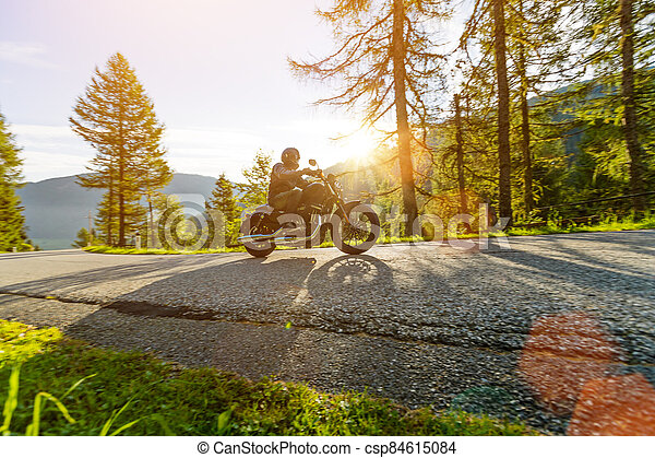 Motorcycle rider driving in Alps, beautiful nature with clear sky. - csp84615084