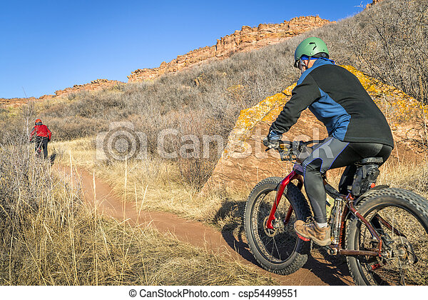 mountain bikers riding trail at Colorado foothills - csp54499551