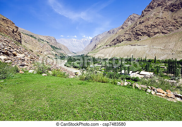 Mountain green meadow and rapid river under blue sky - csp7483580