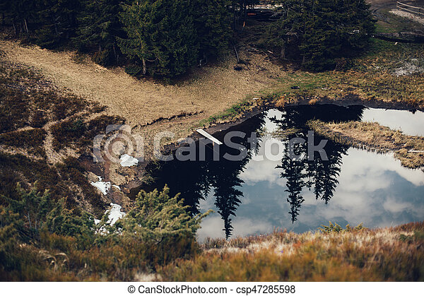 Mountain lake in spruce forest on a background of blue sky - csp47285598
