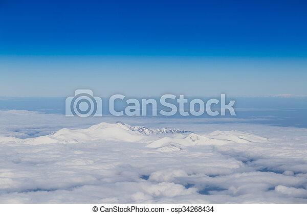 Mountain range emerging from endless white clouds, aerial shot. - csp34268434