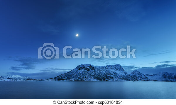 Mountains against blue sky with clouds and moon in winter - csp60184834