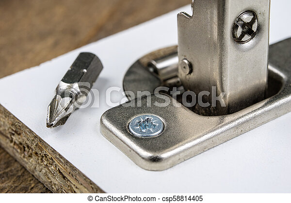 Mounting hinges for chipboard furniture. Joinery accessories used when assembling kitchen furniture. - csp58814405