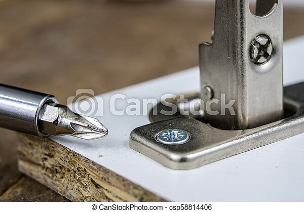 Mounting hinges for chipboard furniture. Joinery accessories used when assembling kitchen furniture. - csp58814406