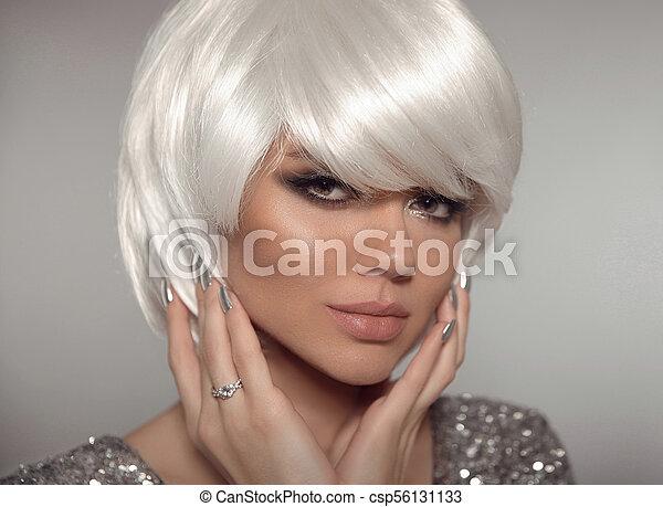 Una mujer rubia con pelo corto y esmalte de uñas. Retrato de chica rubia con pelo blanco presentando anillo de diamantes en el dedo. - csp56131133