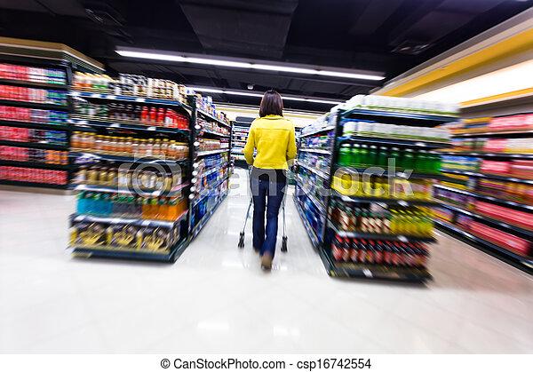 Una mujer joven de compras en el supermercado - csp16742554
