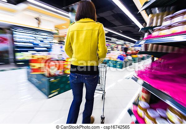 Una joven comprando en el supermercado, con el movimiento borroso - csp16742565