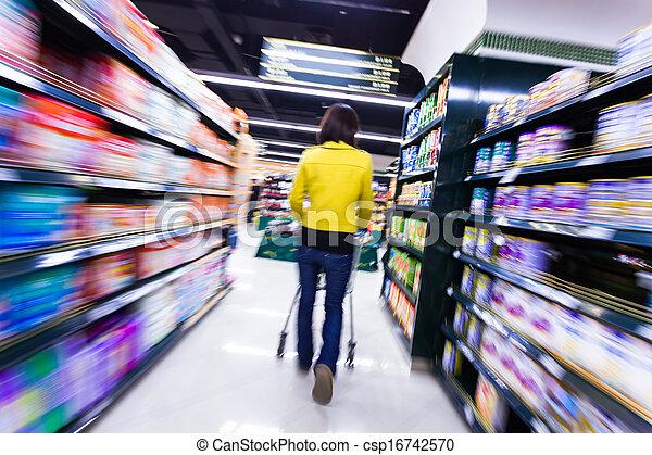 Una joven comprando en el supermercado, con el movimiento borroso - csp16742570