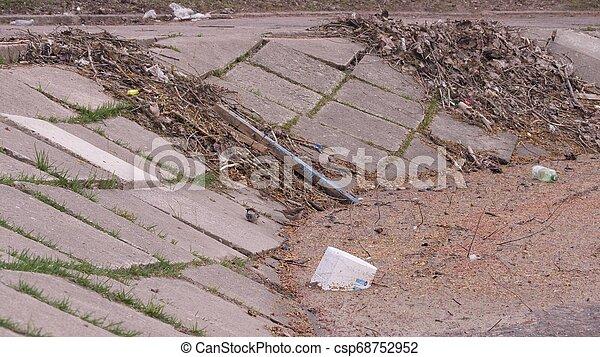 Einige kleine Vögel sitzen und dann vom Ufer des Flusses wegfliegen in einem Stadtpark zwischen Plastikflaschen, Müll und anderen Schadstoffen, die im Wasser schwimmen, als Beispiel für Umweltverschmutzung in langsamem Bewegungszoom 4K Video. - csp68752952