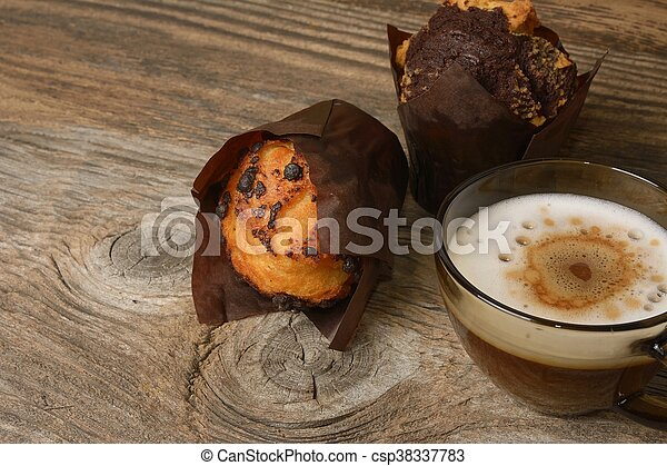 muffins and a cup of coffee on wooden background - csp38337783