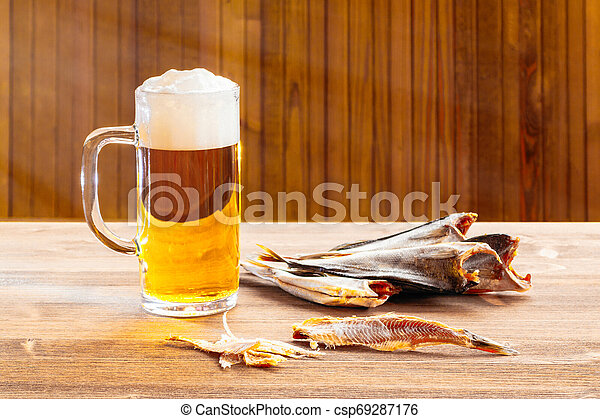 Mug with frothy beer and dried fish on wooden background - csp69287176