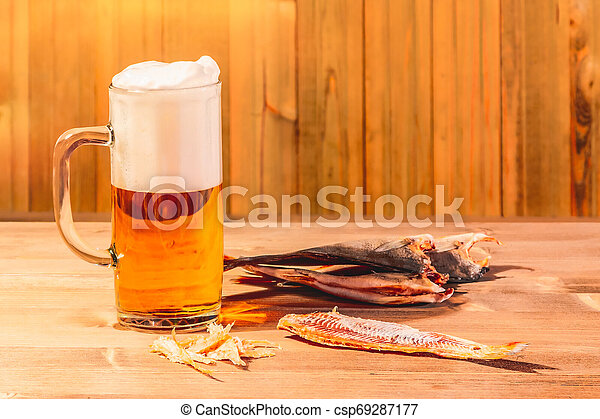 Mug with frothy beer and dried fish on wooden background - csp69287177