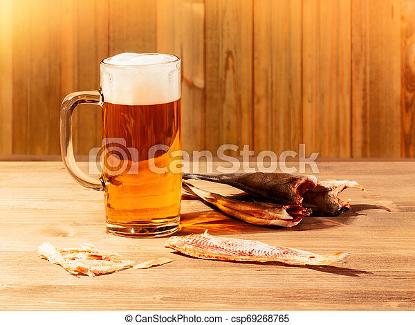 Mug with frothy beer and dried fish on wooden background - csp69268765
