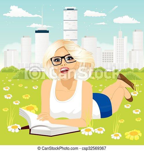 Mujer recostada en el libro de lectura de hierba - csp32569367