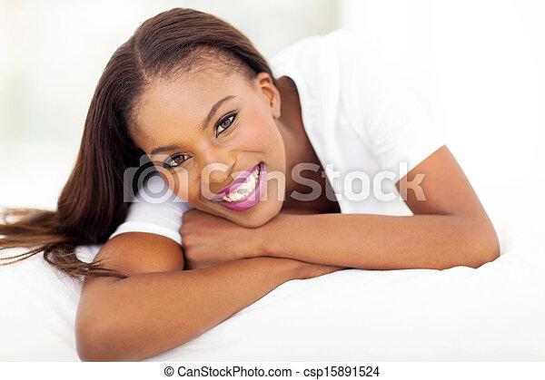 Mujer afroamericana tendida en la cama - csp15891524