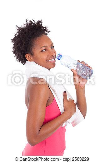 Joven afroamericana en forma de mujer que bebe agua - csp12563229