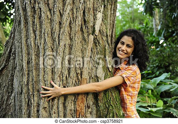 Enamorada de la naturaleza: mujer abrazando a un árbol en el bosque - csp3758921