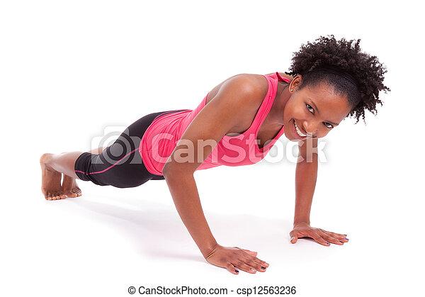 Joven hermosa mujer africana haciendo ejercicios en el piso, aislados en el fondo blanco - csp12563236