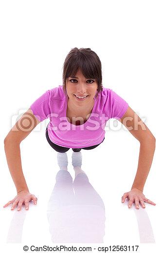 Una joven hermosa mujer caucásica haciendo ejercicios en el suelo, aislada en el fondo blanco - csp12563117