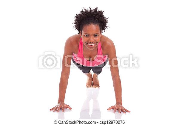 Joven hermosa mujer africana haciendo ejercicios en el piso, aislados en el fondo blanco - csp12970276