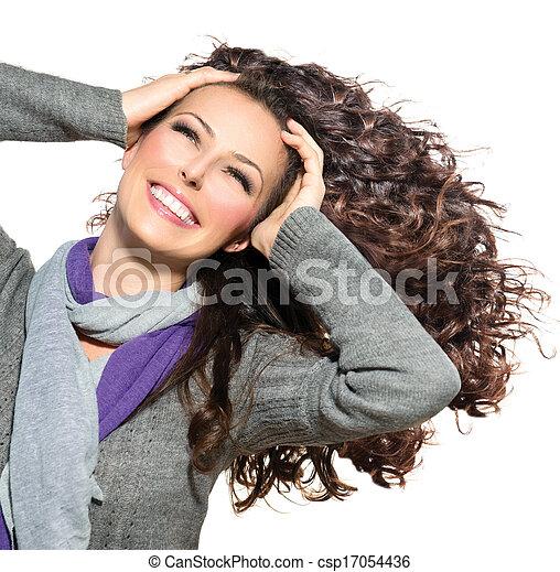 Una mujer hermosa con el pelo largo y rizado. Cabello saludable - csp17054436