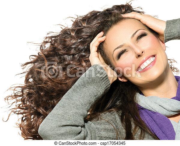 Una mujer hermosa con el pelo largo y rizado. Cabello saludable - csp17054345