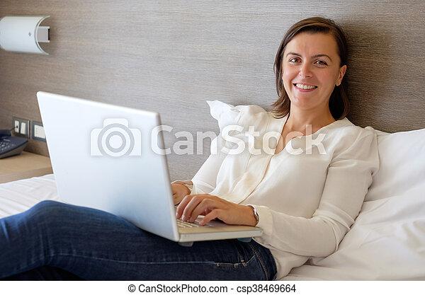 Una mujer alegre usando su portátil en la cama del hotel - csp38469664