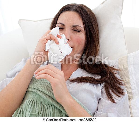Mujer enferma que sopla sobre una cama - csp2835809
