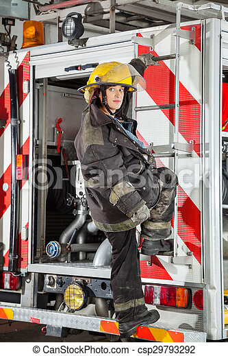 Mujer de fuego parada en el camión en la estación de bomberos - csp29793292