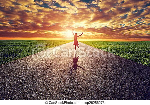 Mujer feliz saltando en largo camino recto, camino hacia el sol del atardecer - csp26256273