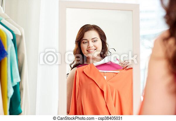 Mujer feliz más grande con camisa en el espejo - csp38405031
