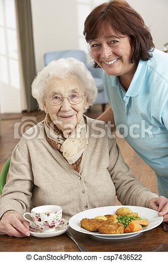 Mujer mayor servida por cuidador - csp7436522