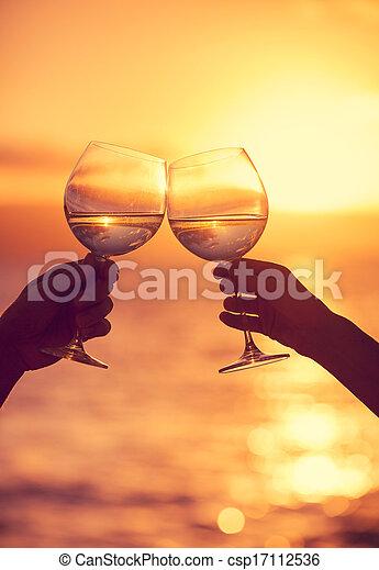 Hombre y mujer tintineando copas de vino con champán al atardecer dramático fondo del cielo - csp17112536