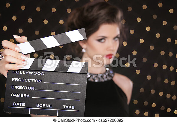 Mano sosteniendo aplausos de cine contra la mujer de la moda con rojo sexy - csp27206892
