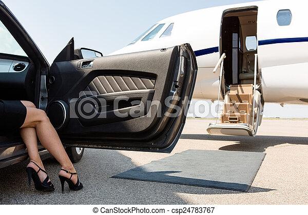 Una mujer rica saliendo del coche en la terminal - csp24783767