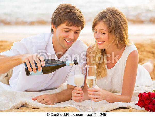 concepto de luna de miel, hombre y mujer enamorados, pareja disfrutando de una copa de champán en la playa tropical al atardecer - csp17112451