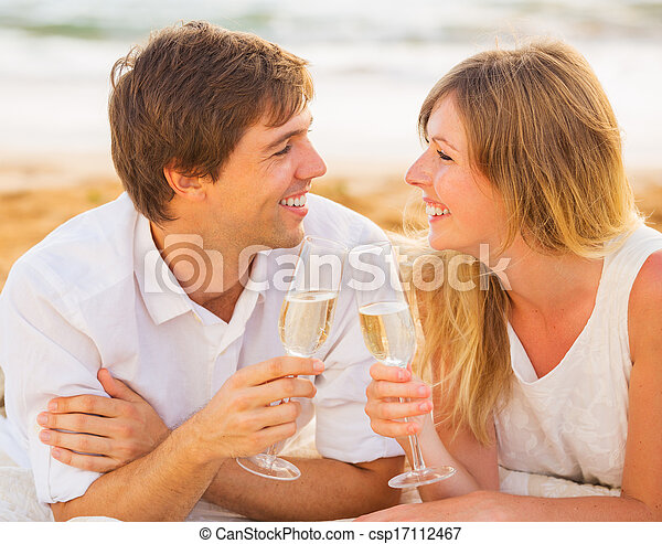concepto de luna de miel, hombre y mujer enamorados, pareja disfrutando de una copa de champán en la playa tropical al atardecer - csp17112467