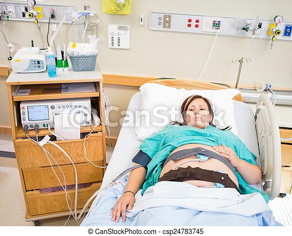 Mujer embarazada siendo monitorizada por la máquina CTG - csp24783745
