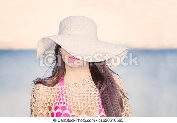 La mujer de la playa de moda con sombrero de sol cubriendo un ojo. - csp20610565
