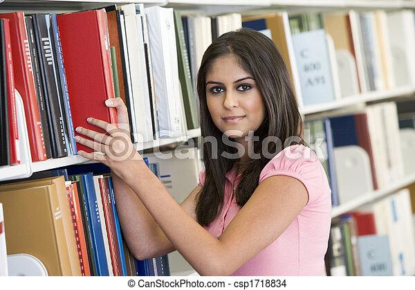 Mujer en la biblioteca sacando un libro de una estantería - csp1718834