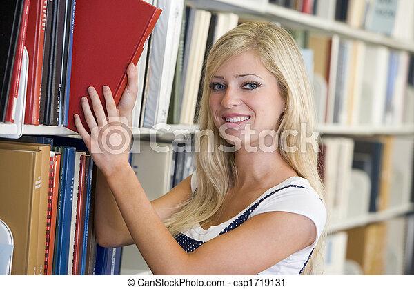 Mujer en la biblioteca sacando un libro de una estantería - csp1719131