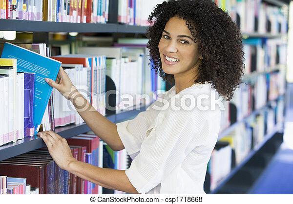 Mujer en la biblioteca sacando un libro de una estantería - csp1718668